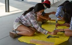 In the breezeway next to the 100s building, sophomore Ashley Kim (left) joins her fellow Associated Student Body [ASB] members in painting a letter on a poster to be used the next day, Friday, Aug. 20, in the Welcome Back assembly. The in-person gathering will be the first to take place in the gym since the coronavirus pandemic closed down schools in March 2020.