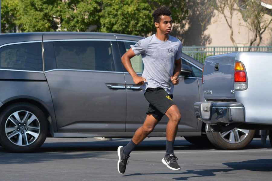 Cross country runner sophomore Jaden Wiggs jogs down the SH parking lot during an Aug. 10 morning cross country practice.