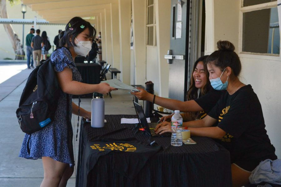 Senior Ashley Hoang (left) hands over her spirit wear form to senior Elaine Chu during Lancer Day on Aug. 10. The Aug. 10-released school health and safety guidelines now allow anyone on campus to be mask-free when outdoors.
