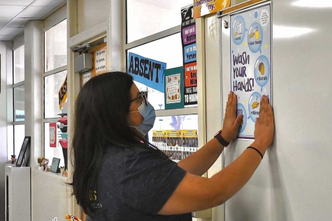In preparation for the first day of school, math teacher Cristian Bueno posts a sign Aug. 13 to remind students of proper hand hygiene in Room 65. The poster, along with another one about indoor masking, was provided by the Fullerton Joint Union High School District as part of its health and safety guidelines for the 2021-2022 school year.