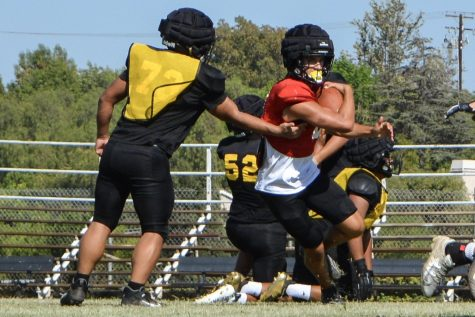 Second-year quarterback senior Max Spero runs with a football while dodging the defense during a summer camp scrimmage Aug. 5 at the Sunny Hills field. The team prepared for its upcoming season with three hour-long practices that began June 21.