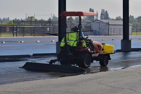 A worker drives a tractor Aug. 9 to repave the Sunny Hills High School parking lot next to the Performing Arts Center as the last step in finalizing the $2.5 million solar panel carport installation.