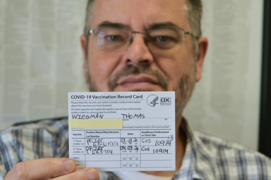 English teacher Tom Wiegman holds up the COVID-19 Vaccination Record Card he received after being vaccinated with the first dose of the Pfizer vaccine in March 2021 and the second dose in April 2021. The Fullerton Joint Union High School District [FJUHSD] sent out an email Sept. 2 to all staff mandating vaccination verification to fulfill a state requirement that the governor signed into law Aug. 11. Anyone working in the FJUHSD who chooses not to be vaccinated must take a COVID-19 test on a weekly basis beginning Oct. 18.