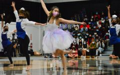 """Dressed as a teacup from """"Beauty and the Beast,"""" senior Eunice Chung leaps alongside her fellow performers during Dance Production's Homecoming performance."""