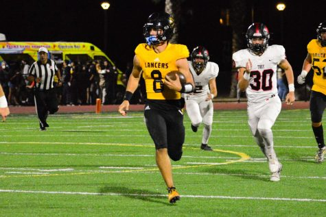 Quarterback senior Max Spero runs to avoid getting tackled during the third quarter of the Oct. 15 game against the Troy Warriors at Buena Park High School Stadium. The Lancers, who were playing in their homecoming game, came away with a 22-20 win that had all the makings of a rivalry affair, especially in a wild two minutes.