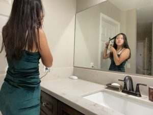 In her deep forest green colored dress, senior Minjeong Kim practices curling her hair in front of the mirror before attending the Homecoming dance on Oct. 16 at the Sunny Hills High School quad.