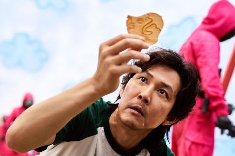 """Gi Hun (Lee Jung Jae, """"Along with the Gods"""") brings his dalgona, a honeycomb-like candy, to the light, and discovers a new way to cut out the umbrella shape during ppopgi, the second round of the competition that comprises """"Squid Game."""""""
