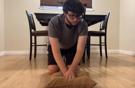 Senior Elijah Ramirez demonstrates CPR chest compressions on a pillow on Sept. 30  in his dining room as a replacement for a dummy or a stuffed animal. Ramirez had to video record himself practicing hands-on CPR and submit a video for review/approval by assistant principal Hilda Arredondo to fulfill a state-mandated graduation requirement.