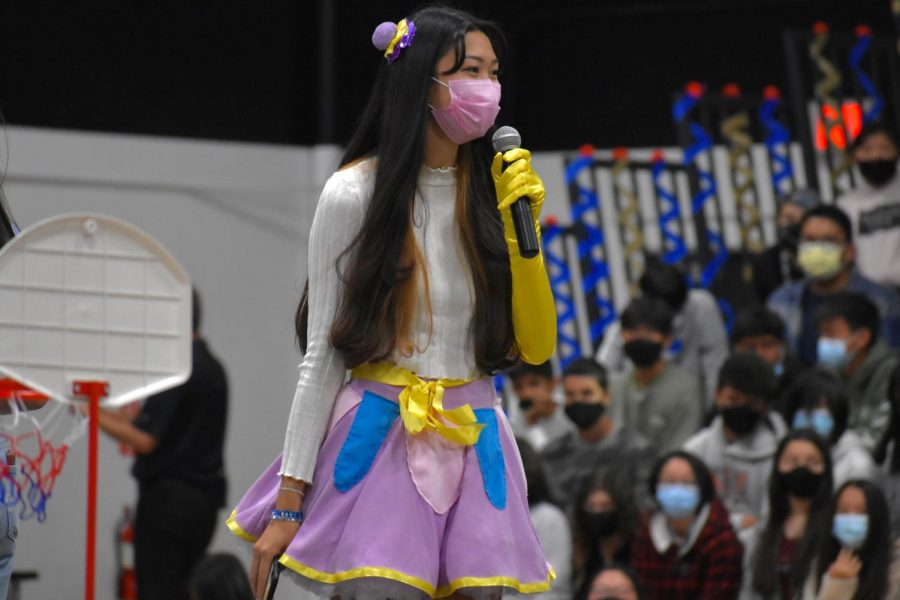 """Associated Student Body [ASB] community affairs commissioner senior Madeline Liu greets the less than 1,000 crowd in the gym during the Friday, Oct. 15, homecoming assembly. Liu was dressed as Mrs. Potts in keeping with the Oct. 16 homecoming dance theme related to Disney's """"Beauty and the Beast."""" This was also the first time Sunny Hills ASB organized a triple assembly schedule to meet state COVID-19 guidelines restricting school indoor events to no more than 1,000 in the audience."""
